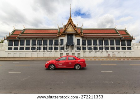 BANGKOK, THAILAND - SEBTEMBER 21, 2013: Taxi on the road in front of the famous Buddhist Temple Wat Phra Kaew, one of the main landmarks of Bangkok, Thailand - stock photo