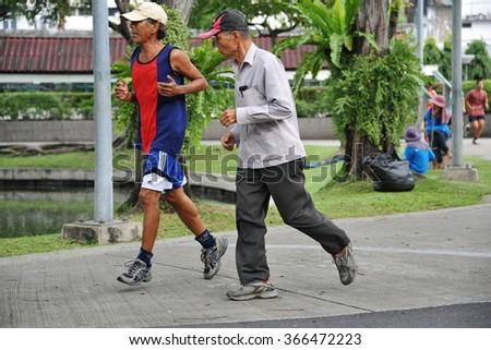 BANGKOK, THAILAND - SEP 29, 2013: Men run through a city centre park. In the highly urbanized Thai capital public public parks are often used by Bangkokians as spaces to exercise.  - stock photo