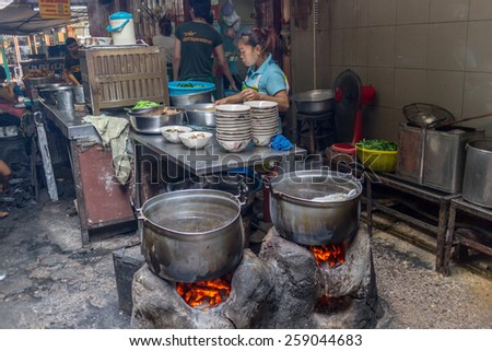 Bangkok, Thailand-Sep 28th 2012: A woman serves food from a street kitchen in Chinatown. There are many such kitchens in the area. - stock photo