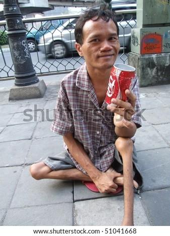 BANGKOK, THAILAND - SEPTEMBER 23: Thai crippled man sits on a path in central Bangkok begging for money with a coke can. September 23 2007 in Bangkok. - stock photo