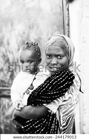 BANJUL, GAMBIA - MAR 14, 2013: Unidentified Gambian lady holds her little daughter on her hands in Gambia, Mar 14, 2013. Major ethnic group in Gambia is the Mandinka - 42% - stock photo