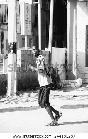 BANJUL, GAMBIA - MAR 14, 2013: Unidentified Gambian man walks in the street n Gambia, Mar 14, 2013. Major ethnic group in Gambia is the Mandinka - 42% - stock photo