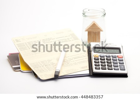 Bank book, calculator, pen, home in jars.The concept of financial planning to buy a home. Financial tools - stock photo