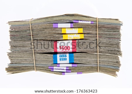 Bank bundles of different denomination dollar bills stacked on top of each other and secured with two rubber bands, side view isolated on white - stock photo
