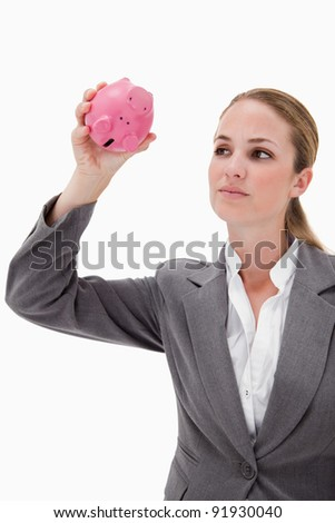 Bank employee taking close look at piggy bank against a white background - stock photo