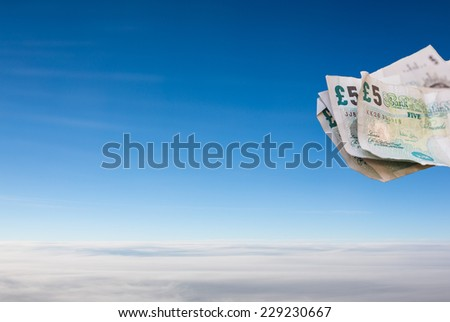 Bank notes floating in a blue sky - stock photo
