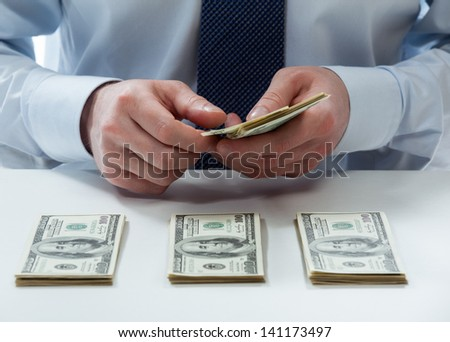 Bank teller's hands counting dollar banknotes on the table - stock photo