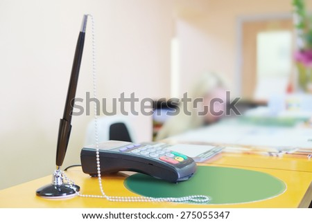 Bank terminal and black pen on the reception desk - stock photo