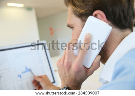 Bank trader negotiating on the phone from office - stock photo