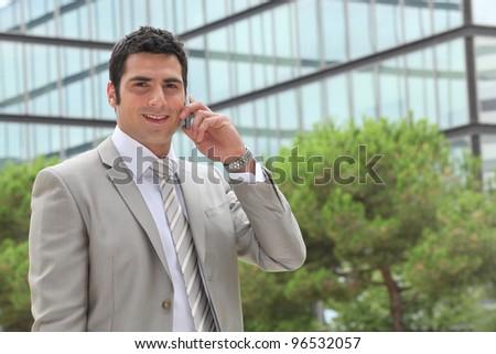 Banker having phone call outdoors - stock photo