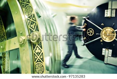 banker is opening safe door - stock photo