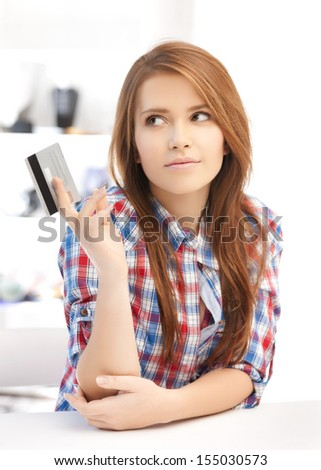 banking and shopping concept - pensive teenage girl with credit card - stock photo