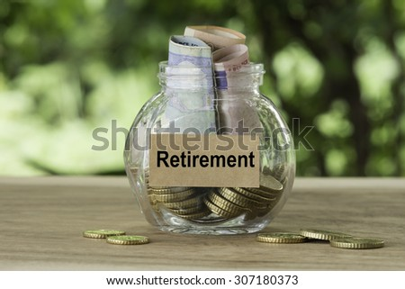 banknote and coins in glass jar with retirement label on nature background, financial concept. - stock photo