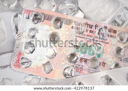 Banknote 1000 Indian rupees on an empty blister pack of tablets - stock photo