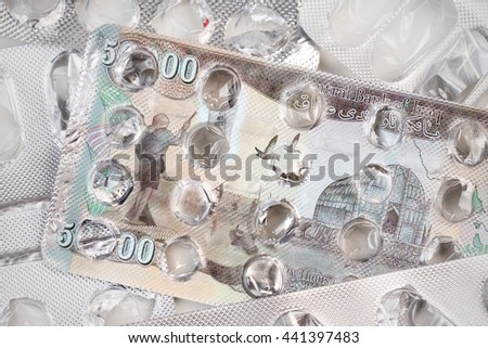Banknote 50000 Iraqi dinars on an empty blister pack of tablets - stock photo