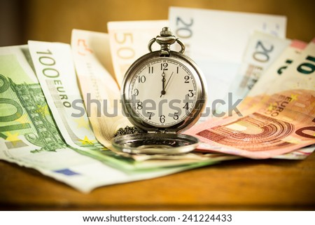 banknotes and a pocket watch on a wooden table - stock photo