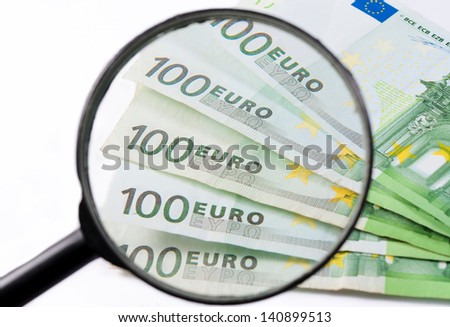 Banknotes of 100 euro enlarged under the magnifier - stock photo