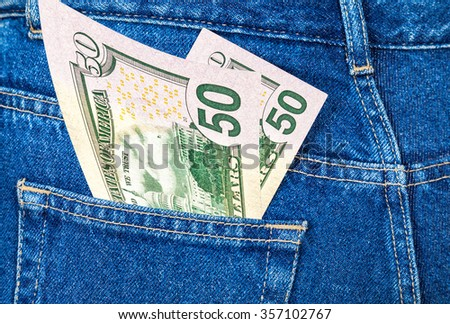 Banknotes of fifty U. S. dollars bill sticking out of the back jeans pocket - stock photo