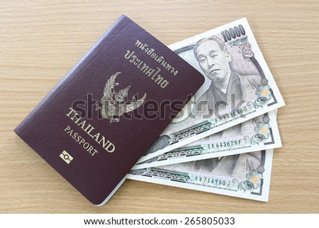 Banknotes of Japan in thai passport on wood background. - stock photo