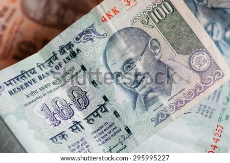Banknotes of one hundred rupees. Selective focus on a portrait of Mahatma Gandhi on the official currency of the Republic of India - stock photo