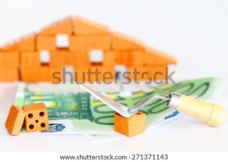 banknotes with brick wall, symbolic house construction - stock photo