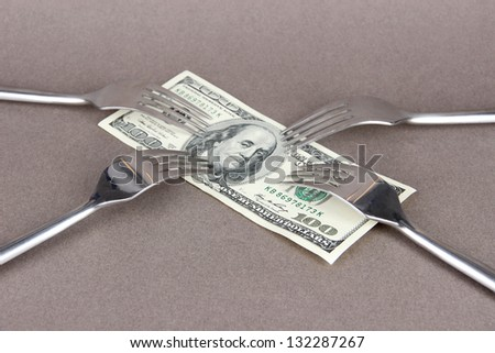 Banknotes with forks on grey background - stock photo