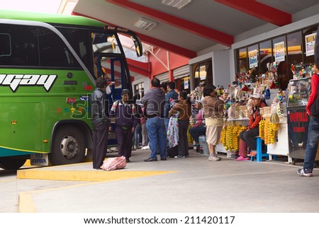 BANOS, ECUADOR - FEBRUARY 22, 2014: Unidentified people at the bus terminal with a bus standing in the back and snack stands on the side on February 22, 2014 in Banos, Ecuador.  - stock photo