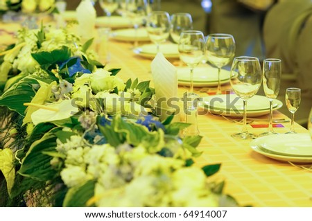 Banquet table arranged with plates, wineglasses and flowers - stock photo
