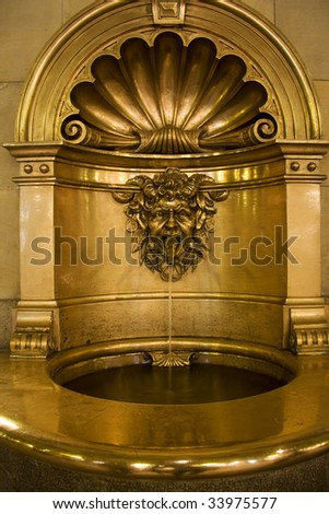 Baptismal font in gold in a church - stock photo