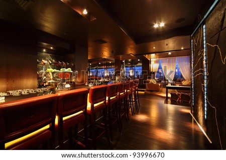 bar counter with chairs in empty comfortable restaurant at night - stock photo