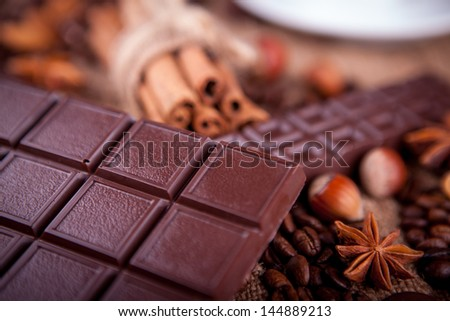 bar of chocolate with cinnamon and coffee beans on a burlap background - stock photo