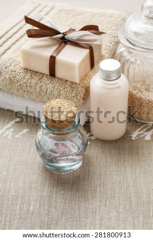 Bar of handmade soap, bottle of essential oil and bottle of liquid soap - stock photo