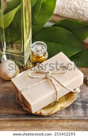 Bar of natural handmade soap and bottle of essential oil on wooden table - stock photo