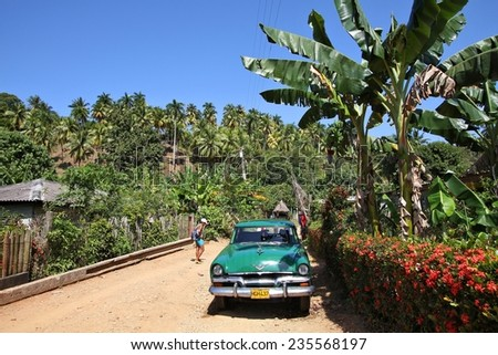 BARACOA, CUBA - FEBRUARY 12, 2011: People walk by oldtimer car in Baracoa, Cuba. Cuba has one of the lowest car-per-capita rates (38 per 1000 people in 2008).  - stock photo