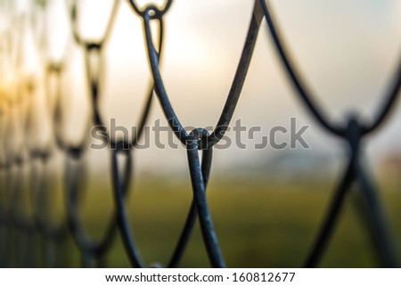 Barb wire fence sunset. - stock photo