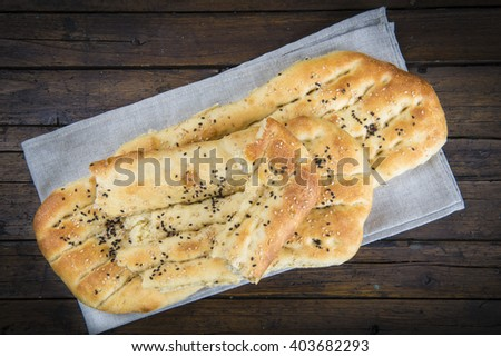 Barbari or Persian bread covered with sesame seeds on the table - stock photo