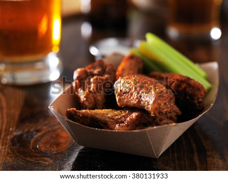 barbecue chicken wings with celery in basket on restaurant table - stock photo