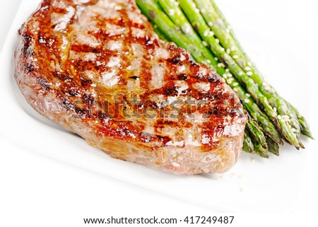 Barbecue grilled beef steak meat with asparagus on white plate close up - stock photo