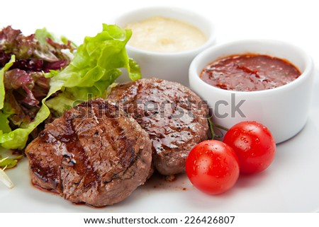 Barbecue grilled beef steak meat with vegetables and sauces. - stock photo