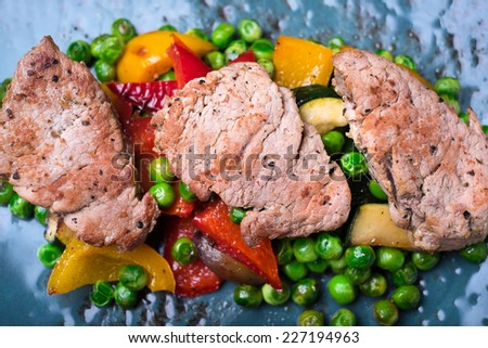 Barbecue Grilled Beef Steak Meat with Vegetables, roasted bell pepper, zucchini or courgette, green peas - stock photo