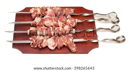 barbecue, raw juicy slices of meat on skewers with sauce on kitchen board - stock photo