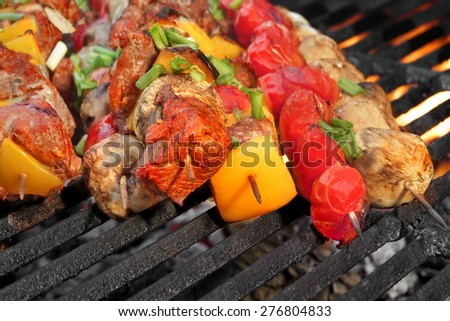 Barbecue Roasted Meat Shish Kebabs With Peppers, Tomatoes and Mushrooms On The Hot Grill. Good Snack For Outdoor Summer Barbecue Party Or Picnic - stock photo