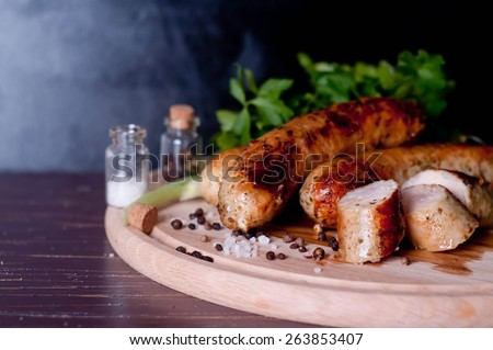 Barbecue tongs with sausages - stock photo