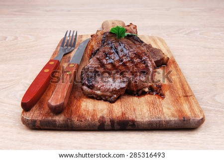barbecued beef fillet on wooden plate with cutlery over table - stock photo