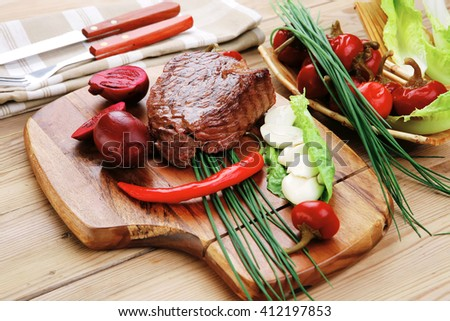 barbecued meat : beef ( lamb ) garnished with green lettuce and red chili hot pepper on wooden table with cutlery - stock photo