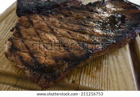 Barbecued steak resting on wooden cutting board. - stock photo