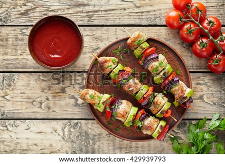 Barbecued turkey or chicken meat shish kebab skewers with ketchup sauce, chopped parsley and tomatoes on rustic wooden table background. Traditional barbecue grill food - stock photo