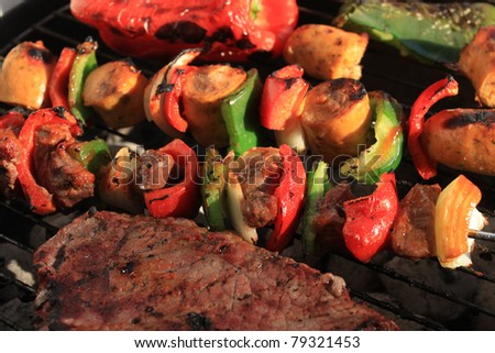 Barbecuing shish kabobs with sausage, steak and peppers, in green and red on a portable charcoal bbq - stock photo