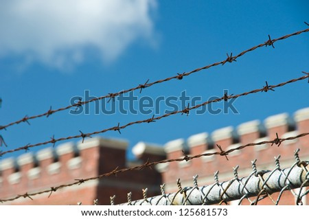 Barbed wire and fence on castle and sky background - stock photo