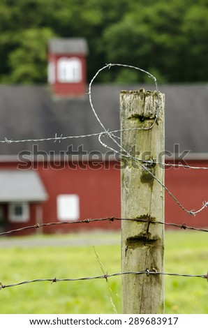 Barbed wire fence at farm with barn in distance. - stock photo